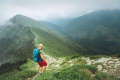 Uomo della viandante di viaggiatore con zaino e sacco a pelo che cammina dal percorso nuvoloso nebbioso della catena montuosa del fotografia stock libera da diritti