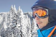 Uomo dello sciatore nel rivestimento, nel casco e nei vetri blu di corsa con gli sci contro panorama della foresta della neve Immagine Stock