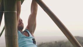 Uomo dello sportivo che fa esercizio addominale mentre addestramento dell'ABS sulla barra trasversale di legno all'aperto Stomaco video d archivio