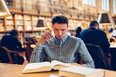 Uomo dello studente che si siede sullo scrittorio nella sala di lettura delle biblioteche e che fa i libri di lettura di ricerca Immagine Stock