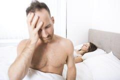 Uomo depresso che si siede sull'orlo del letto in camera da letto Immagini Stock Libere da Diritti
