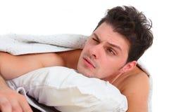 Uomo depresso che si trova a letto immagini stock libere da diritti