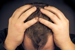 Uomo depresso il suo fronte delle mani Immagini Stock Libere da Diritti