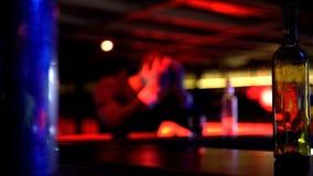 Uomo deprimente che beve da solo in night-club, pensante sopra i problemi, defocused immagini stock