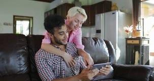 Uomo di abbraccio della donna che si siede sulla vettura Using Tablet Computer che parla nel salone, giovane coppia nella mattina archivi video