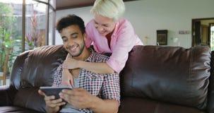Uomo di abbraccio della donna che si siede sulla vettura Using Tablet Computer che parla nel salone, giovane coppia nella mattina video d archivio
