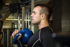 Uomo di addestramento di allenamento dell'oscillazione di Kettlebell alla palestra Immagine Stock