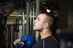 Uomo di addestramento di allenamento dell'oscillazione di Kettlebell alla palestra Fotografie Stock