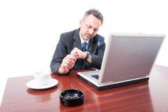 Uomo di affari all'ufficio che fuma e che controlla tempo Fotografia Stock Libera da Diritti