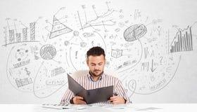 Uomo di affari allo scrittorio con i grafici disegnati a mano Fotografia Stock Libera da Diritti