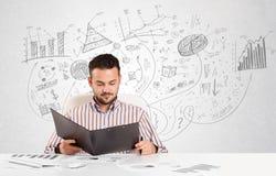 Uomo di affari allo scrittorio con i grafici disegnati a mano Fotografie Stock