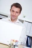 Uomo di affari allo scrittorio con il computer portatile Fotografie Stock Libere da Diritti