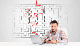 Uomo di affari allo scrittorio con il labirinto e la freccia Immagine Stock