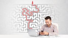 Uomo di affari allo scrittorio con il labirinto e la freccia Fotografia Stock