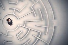 Uomo di affari bloccato in un labirinto circolare immagini stock libere da diritti