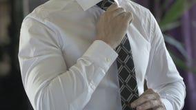 Uomo di affari in camicia bianca che corregge il suo legame archivi video