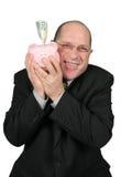 Uomo di affari che abbraccia la Banca Piggy Fotografie Stock