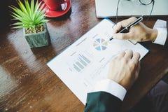 Uomo di affari che analizza i grafici ed i grafici di reddito fotografie stock libere da diritti