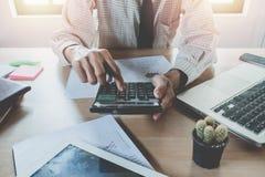 Uomo di affari che analizza i grafici di investimento e che per mezzo del calcolatore Immagini Stock