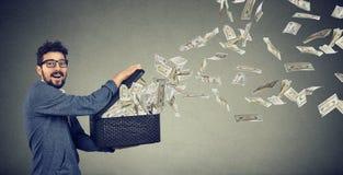 Uomo di affari che apre una scatola che lascia le banconote del dollaro volare via Fotografie Stock Libere da Diritti