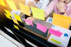 uomo di affari che attacca le note adesive sulla parete di vetro in ufficio e Immagini Stock