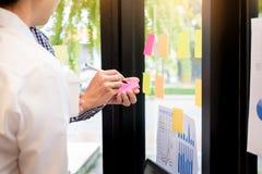 uomo di affari che attacca le note adesive sulla parete di vetro in ufficio e Fotografia Stock