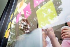 uomo di affari che attacca le note adesive sulla parete di vetro in ufficio e Fotografie Stock Libere da Diritti
