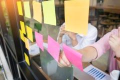uomo di affari che attacca le note adesive sulla parete di vetro in ufficio e Immagine Stock