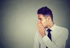 Uomo di affari che bisbiglia un segreto del gossip a qualcuno Immagine Stock
