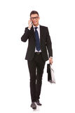 Uomo di affari che cammina e che comunica sul telefono Immagine Stock Libera da Diritti