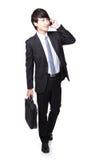 Uomo di affari che cammina mentre parlando telefono Fotografia Stock