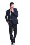 Uomo di affari che cammina mentre tenendo una mano al suo mento Fotografia Stock Libera da Diritti