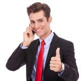 Uomo di affari che comunica sul telefono e che fa bene Fotografia Stock Libera da Diritti