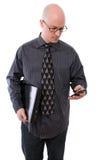 Uomo di affari che controlla il suoi telefono mobile e computer portatile Fotografia Stock