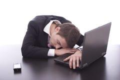 Uomo di affari che dorme sopra il computer portatile Fotografia Stock