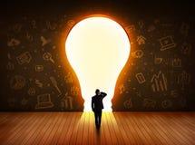 Uomo di affari che esamina la lampadina della luce intensa nella parete Immagine Stock Libera da Diritti