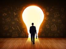 uomo lampadina : Uomo di affari che esamina la lampadina della luce intensa nella ...