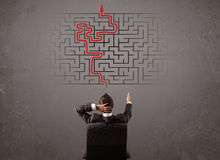 Uomo di affari che esamina un labirinto e l'uscita Immagini Stock