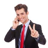 Uomo di affari che fa il segno di vittoria sul telefono Immagini Stock