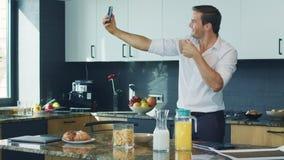 Uomo di affari che fa la foto del selfie in cucina Uomo felice che prende foto in casa stock footage