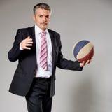 Uomo di affari che gioca con una pallacanestro al immagini stock