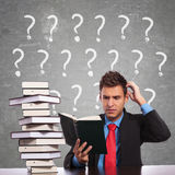Uomo di affari che graffia suo capo mentre leggendo Immagini Stock