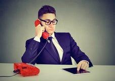 Uomo di affari che ha conversazione telefonica seria e che per mezzo del computer della compressa fotografie stock libere da diritti