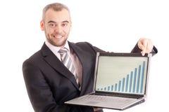 Uomo di affari che indica ad un computer portatile con il grafico Fotografia Stock