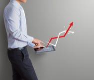 Uomo di affari che indica compressa con l'aumento del grafico della freccia Immagini Stock Libere da Diritti