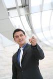 Uomo di affari che indica con l'edificio per uffici Fotografia Stock Libera da Diritti