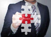Uomo di affari che indica sulla conformità di parola scritta del puzzle Fotografie Stock