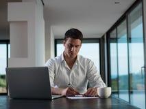 Uomo di affari che lavora al computer portatile a casa Fotografia Stock Libera da Diritti