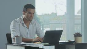 Uomo di affari che lavora al computer portatile Uomo concentrato che redige i documenti archivi video