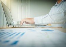 Uomo di affari che lavora all'ufficio con il computer portatile ed ai documenti sul suo fotografie stock libere da diritti